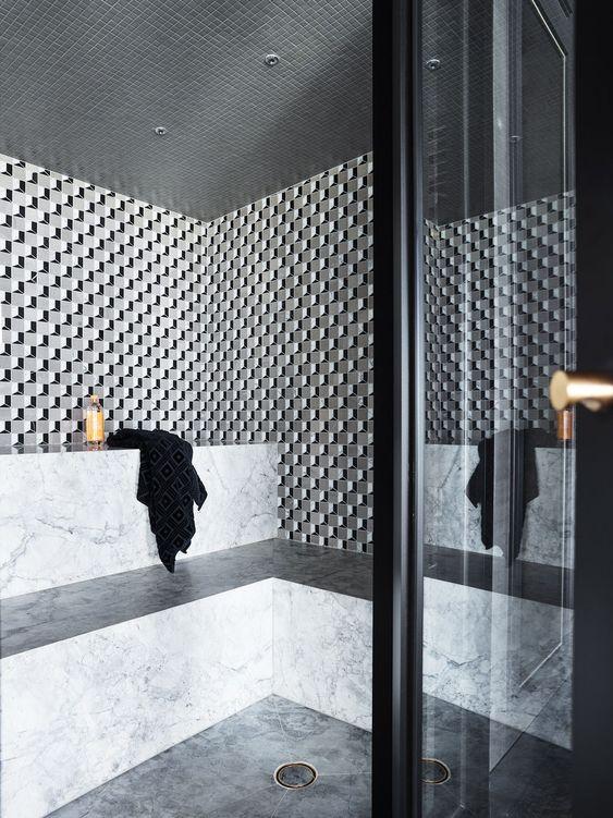 un elegante bagno turco rivestito con piastrelle in marmo e mosaico e con lunghe panchine lungo le pareti