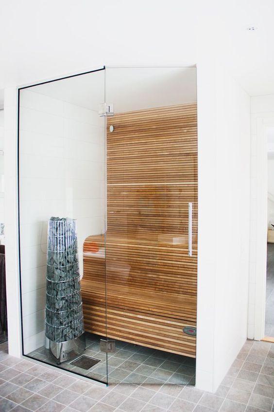 un piccolo bagno turco minimalista rivestito in legno e con panche curve e pareti di vetro è bello