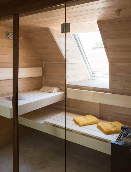 un piccolo bagno turco domestico rivestito di legno tinto chiaro e un paio di panchine più una piccola finestra per la luce naturale