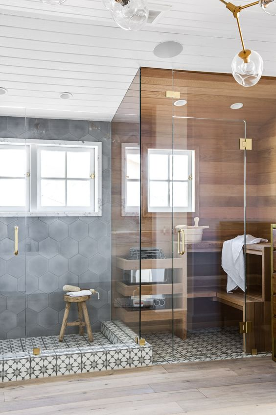 un bagno turco minuscolo ma chic ricoperto di legno, con due panchine e una finestra più tocchi d'oro