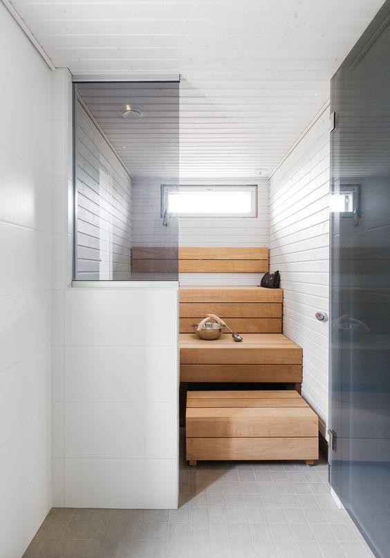 un bagno turco minuscolo ma chic rivestito di legno tinto di luce e bianco, con panchine e un piccolo lucernario