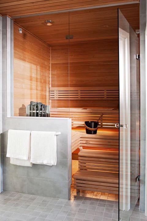 un minuscolo bagno turco rivestito in legno, con panchine e luci incorporate sotto i gradini