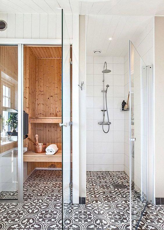 una minuscola sauna domestica rivestita di legno tinto di luce, con una finestra, tessere di mosaico e panchine galleggianti
