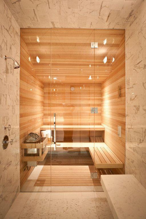 un accogliente bagno turco completamente rivestito in legno, con alcune panchine e luci incorporate più porte in vetro è incredibile