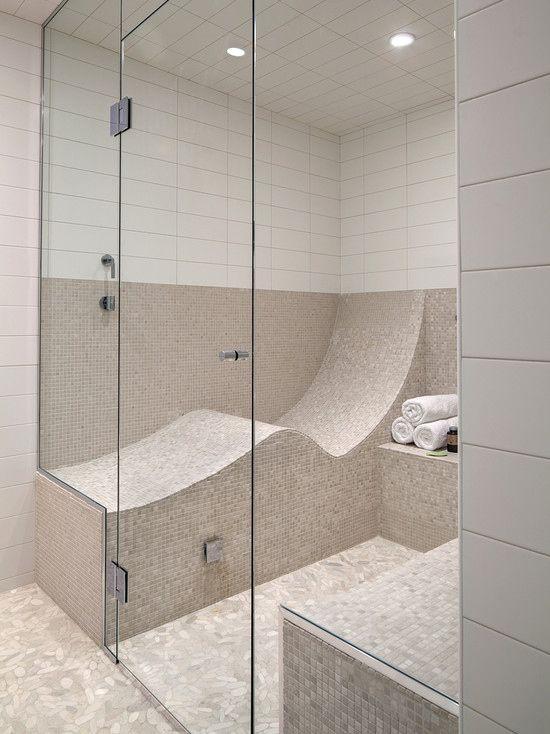 un elegante bagno turco neutro rivestito con un piccolo mosaico e piastrelle bianche della metropolitana, con panchine curve rivestite di piastrelle che sono molto confortevoli