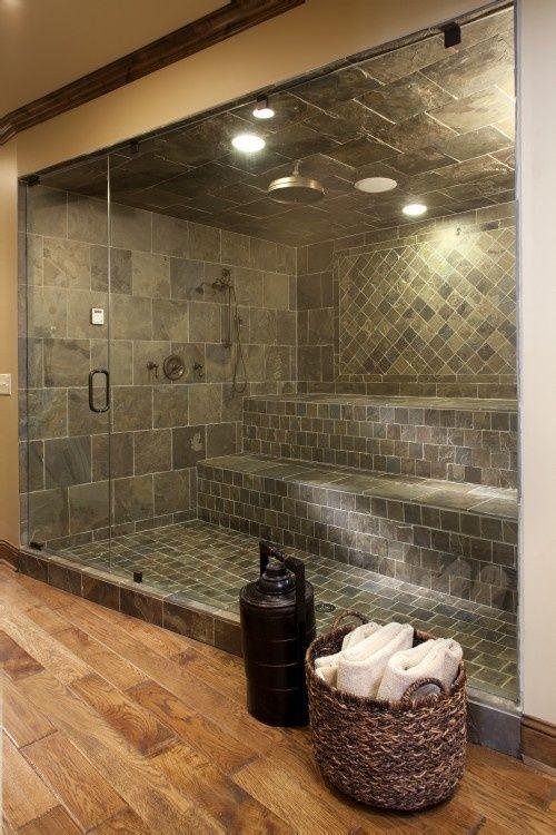 un grande bagno turco rivestito con piastrelle grigie in vari motivi e con un'unica grande panca più una porta a vetri è molto bello