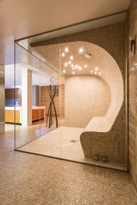 un elegante bagno turco neutro rivestito con piastrelle di piccola scala, con un'unica panca che appare curva dal muro