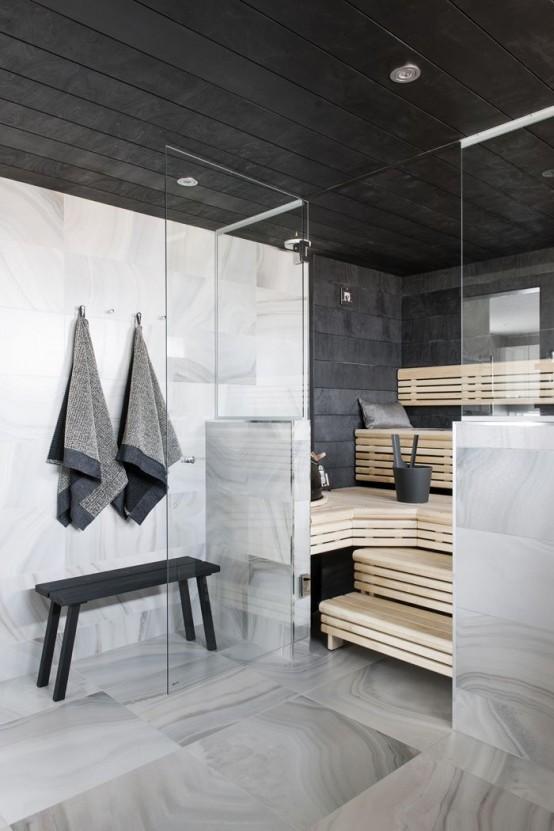 un bagno turco rivestito con piastrelle nere e con panche in legno su più livelli più luci incorporate
