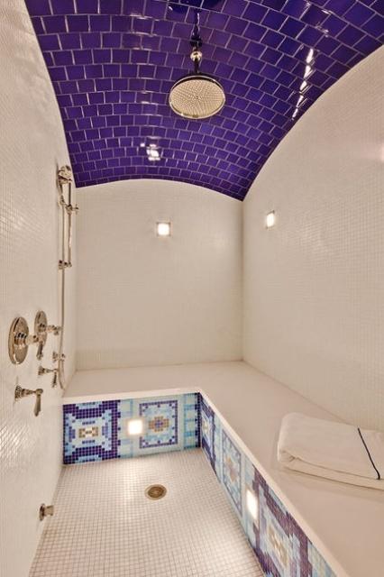 un audace bagno turco rivestito con piastrelle viola e bianche, con una grande panca rivestita di piastrelle e alcuni motivi su tutta la panchina