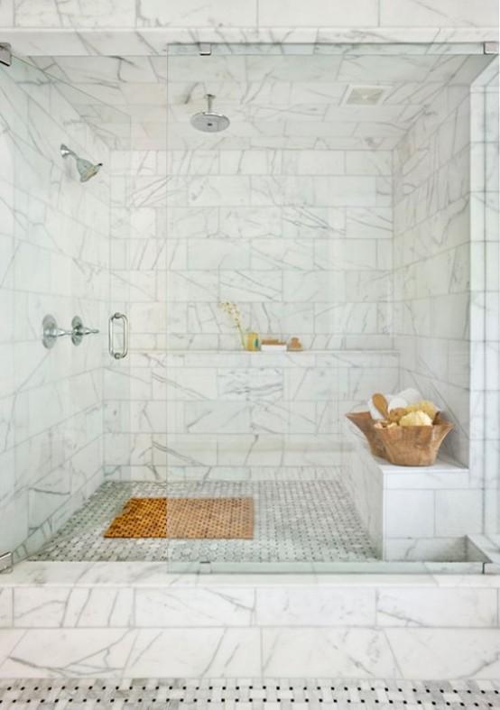 un raffinato bagno turco in marmo bianco con panca rivestita di piastrelle e mensola e ciotole di legno con schiume e scrub