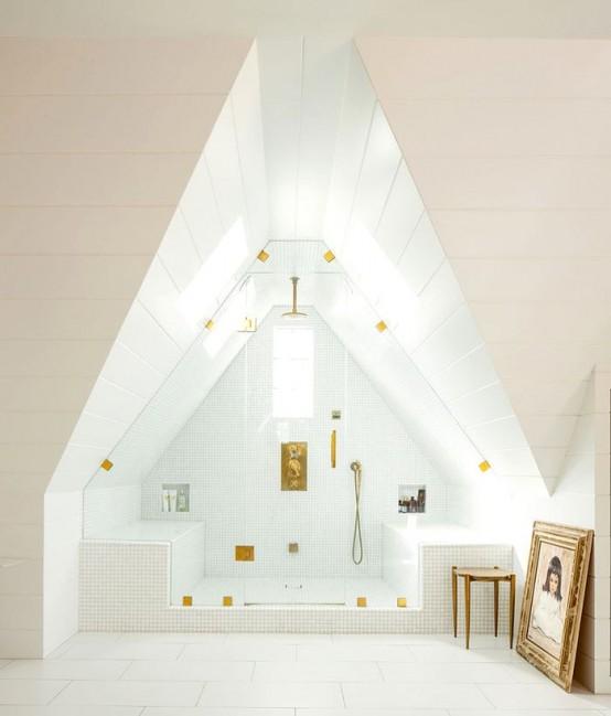 un bagno turco bianco mansardato con una finestra, due panche rivestite di piastrelle e infissi d'oro sembra arioso e chic