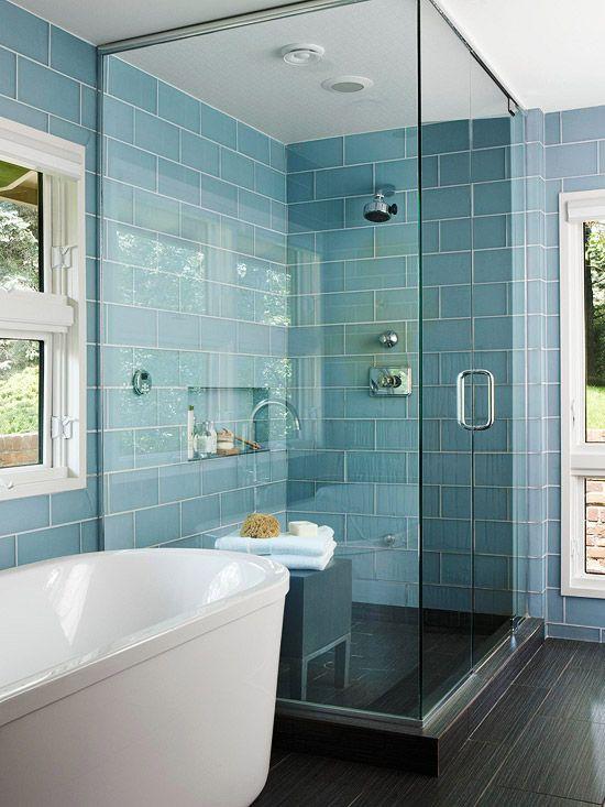 un piccolo bagno turco con piastrelle blu e nere, con una nicchia incorporata per la conservazione e una panca di legno