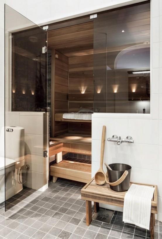 un piccolo bagno turco rivestito in legno, con panchine su diverse panchine e luci incorporate e porte in vetro fumé