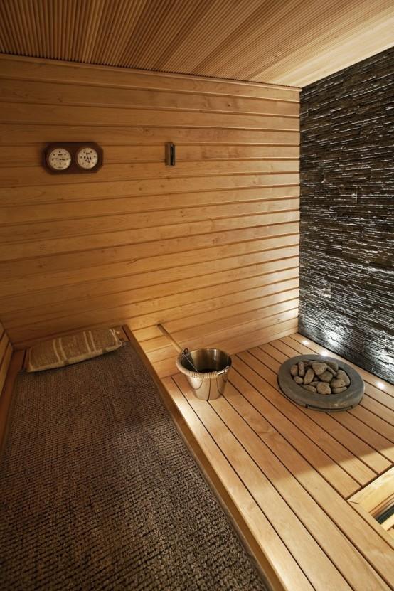 un accogliente bagno turco rivestito in legno con un muro di pietra e diverse panchine, con una copertura di iuta su una di esse e alcune luci