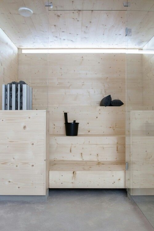 un piccolo bagno turco rivestito in legno e con panchine a gradini più uno stretto lucernario per un'atmosfera più naturale qui