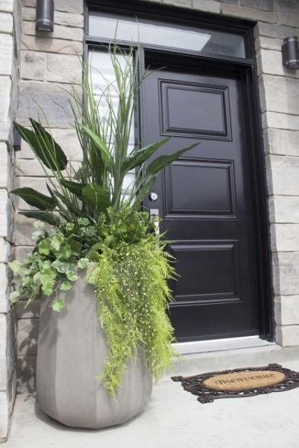 un'alta fioriera sfaccettata in cemento con molta vegetazione è una splendida soluzione per uno spazio moderno