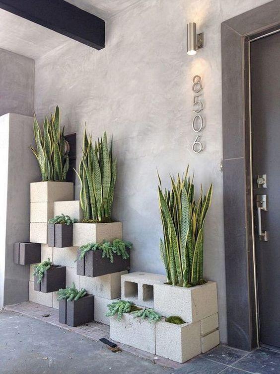 eleganti fioriere in cemento impilate in grigio e nero con vari tipi di piante cambieranno totalmente il tuo spazio esterno