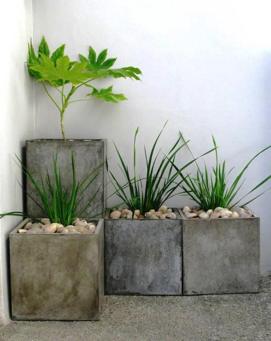 una disposizione di fioriera quadrata in cemento con vegetazione e ciottoli è una decorazione minimalista fresca per un cortile