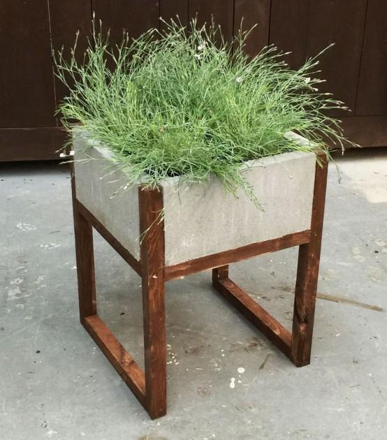 una fioriera in cemento su gambe in legno con erbe è un pezzo moderno ed elegante per uno spazio esterno moderno