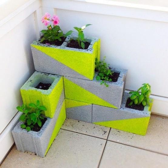 fioriere in cemento accatastate con tocchi geometrici al neon e fiori e vegetazione daranno un'atmosfera minimalista al tuo spazio