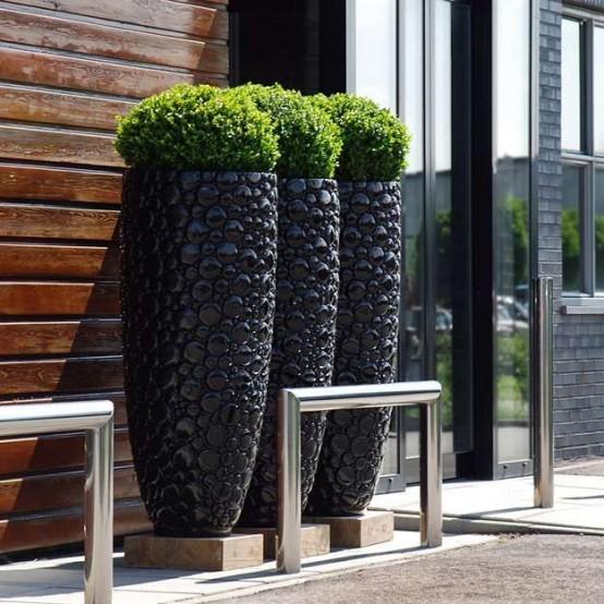Le fioriere nere alte ultra-moderne con un motivo a bolle sono decorazioni chic e audaci da rock per l'esterno