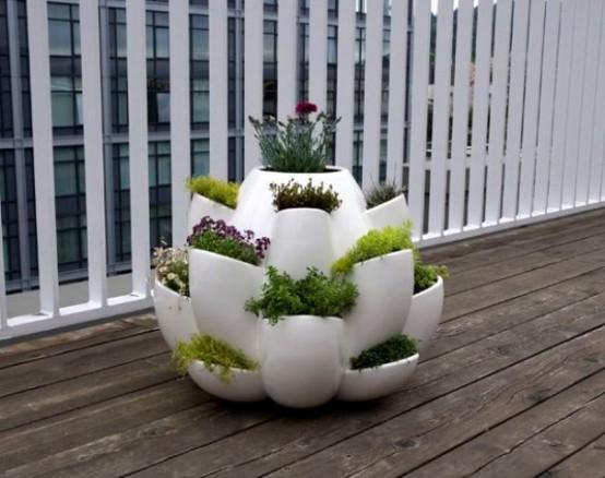 una fioriera rotonda bianca con molte mini fioriere con vegetazione è un pezzo moderno molto eccentrico