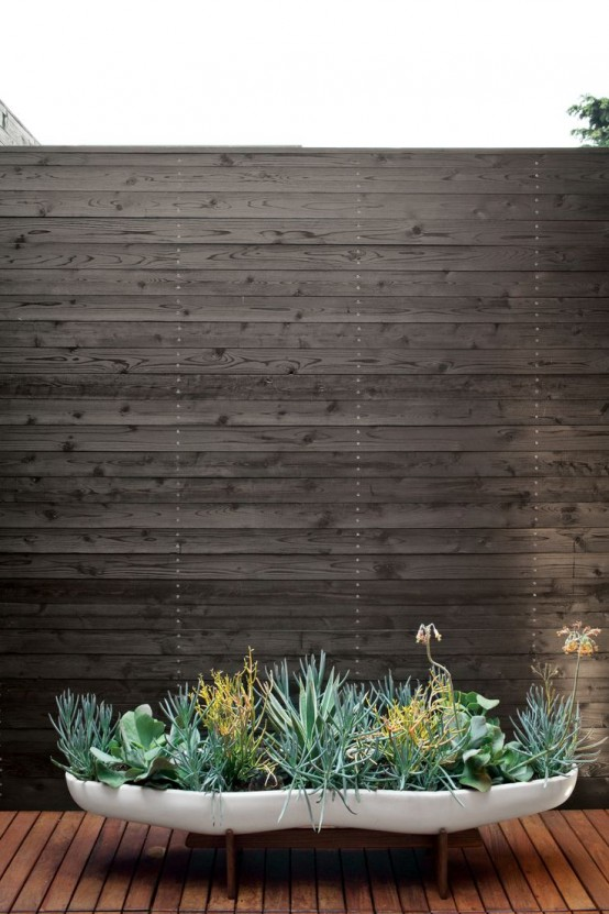 una fioriera bianca bassa e curva lunga con piante grasse e vegetazione è un pezzo molto interessante per qualsiasi spazio moderno