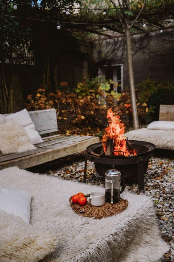 un patio autunnale con panche in legno, pelliccia sintetica, un pozzo del fuoco e alcuni cuscini è super accogliente