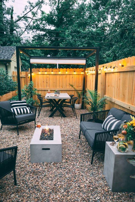 un patio moderno della metà del secolo con ghiaia, un pozzo del fuoco, mobili in rattan nero e luci lungo tutto il recinto
