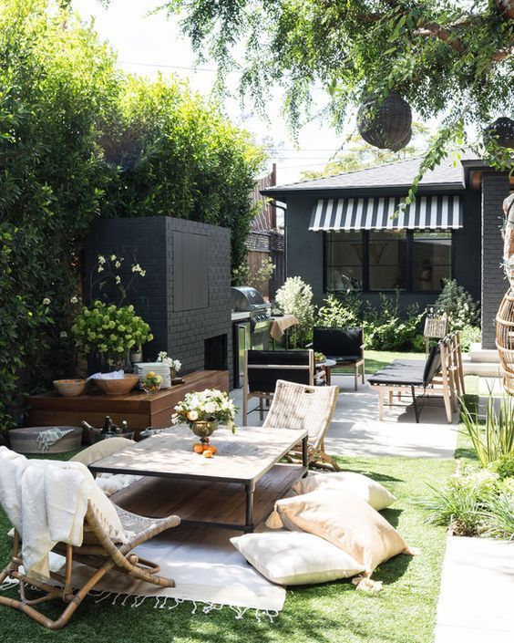 un piccolo patio che comprende una zona soggiorno e una zona camino realizzati in diversi stili e colori contrastanti