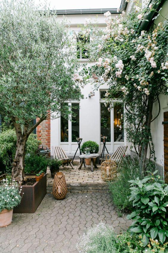 un cortile semplice e moderno con mobili in legno, alcune candele in grandi lanterne a candela e alberi e fiori