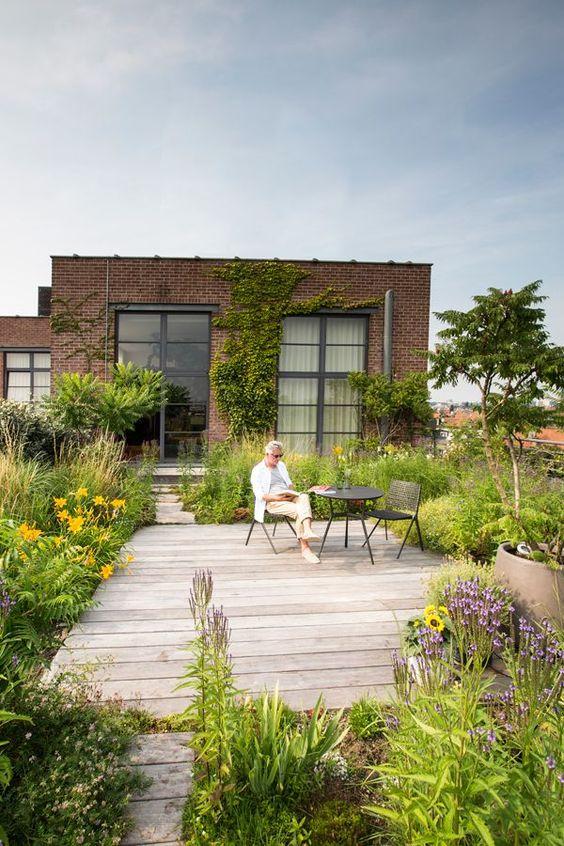 un piccolo e accogliente patio con tanto verde e fiori luminosi, con un ponte in legno e alcuni mobili semplici