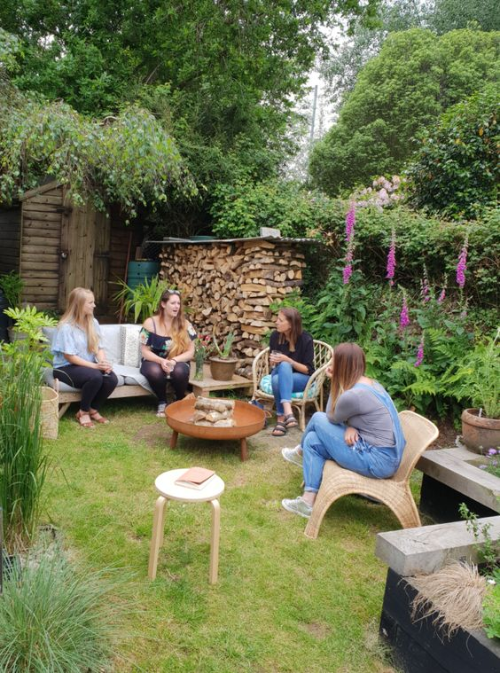 un cortile rustico con un prato verde con mobili in legno e rattan, con molto verde e fiori luminosi