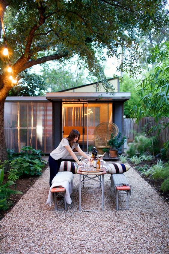un patio moderno con vegetazione e alberi, panchine in legno e metallo e un tavolo da pranzo più cuscini a righe