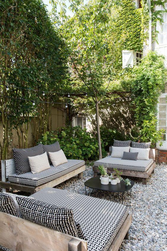 un patio monocromatico con mobili in bianco e nero e molta vegetazione intorno