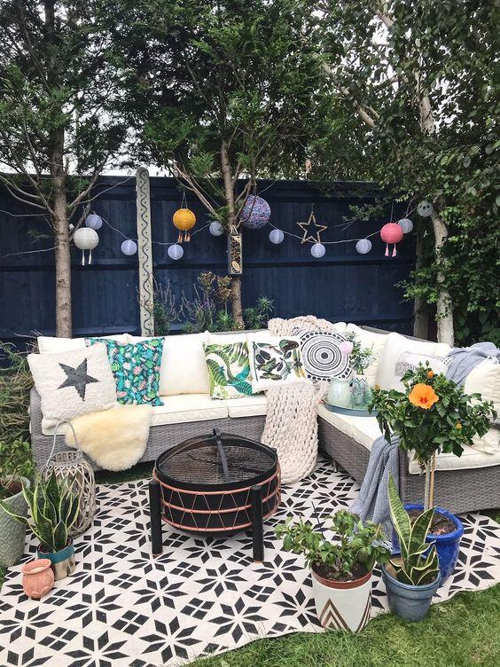 un piccolo patio con un prato verde, lampade di carta, un divano di vimini con cuscini stampati e piante in vaso