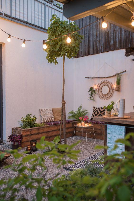 un piccolo patio boho con ghiaia a terra, una panca ad angolo in legno, un po 'di verde, luci, cuscini boho e luci