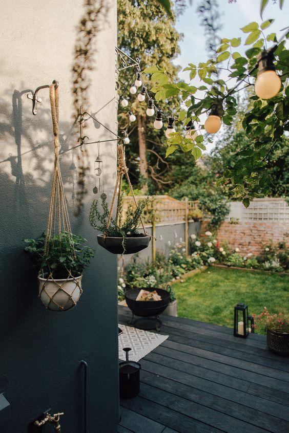 un piccolo cortile nordico con un ponte nero, un pozzo del fuoco, lanterne a candela, un prato verde e molti fiori