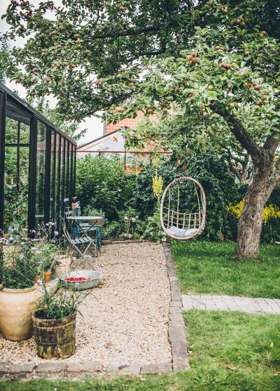 un piccolo cortile con una sedia sospesa, alcuni mobili da giardino, fiori in vaso e un prato verde