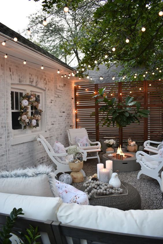 un piccolo patio eclettico con un pozzo del fuoco, alcuni mobili vintage bianchi e luci in tutto lo spazio