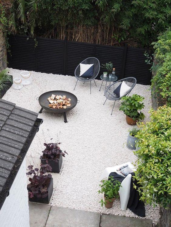 un piccolo patio moderno con ghiaia bianca, sedie in rattan, un pozzo del fuoco e alcune piante in vaso è super elegante