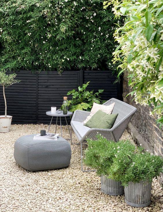 un piccolo patio moderno con ghiaia per terra, con mobili in rattan e piante e fiori in vaso