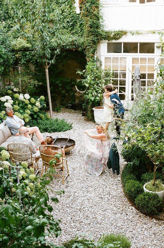 un patio piccolo ma accogliente con ghiaia per terra, alcuni mobili in rattan e molta vegetazione e fiori bianchi intorno