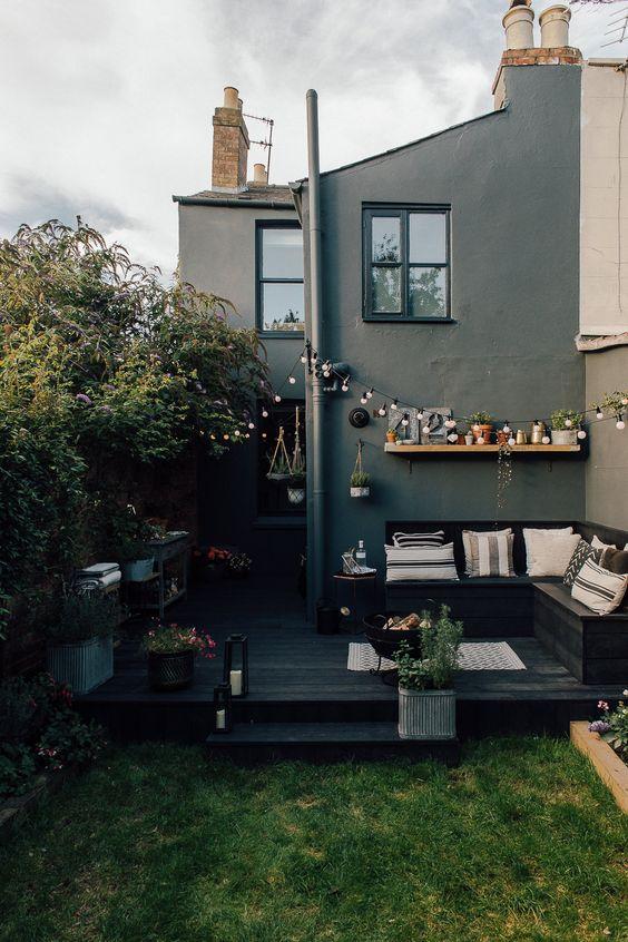 un piccolo cortile scandinavo con un ponte nero, una panchina d'angolo nera, un prato verde e alcune fioriture tutt'intorno