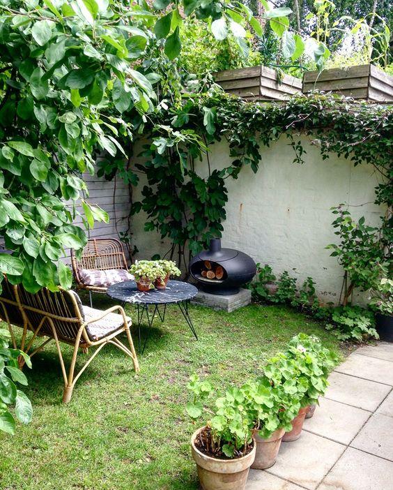 un piccolo ma accogliente cortile con mobili in rattan, un tavolo con piano in marmo, un piccolo focolare e un prato verde