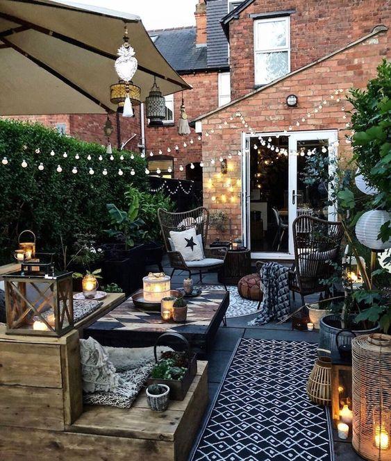uno spazio piccolo ma elegante nel patio con un ponte in legno, molta vegetazione, luci, candele e semplici mobili in legno