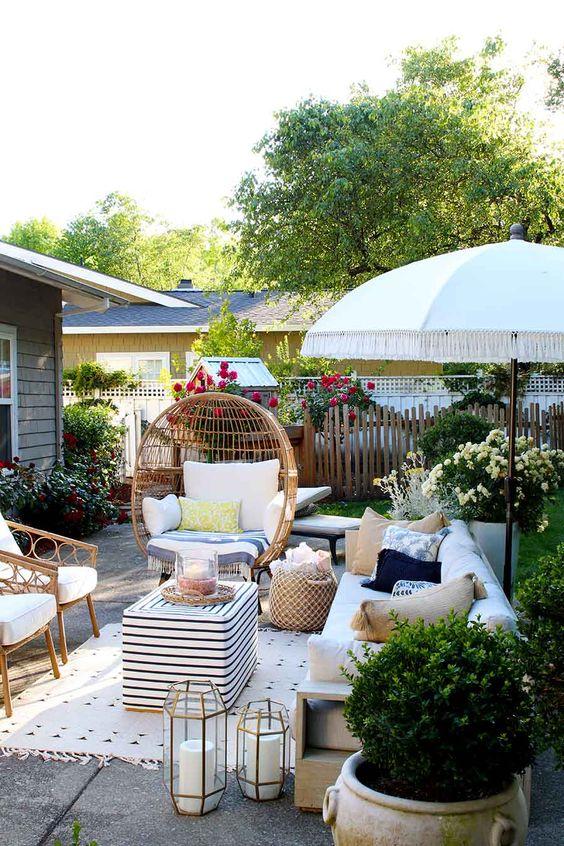 un patio estivo con mobili in rattan, candele, piante in vaso e fiori luminosi tutt'intorno