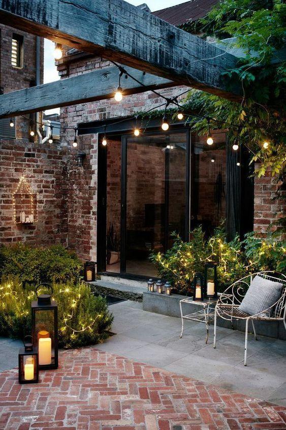 un piccolo patio chic rivestito di cemento e mattoni, con vegetazione e luci e lanterne a candela sembra invitante