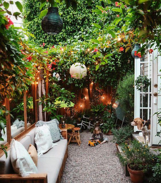 un piccolo cortile molto accogliente con molta vegetazione e fiori, luci, lampade di carta e alcuni mobili comodi