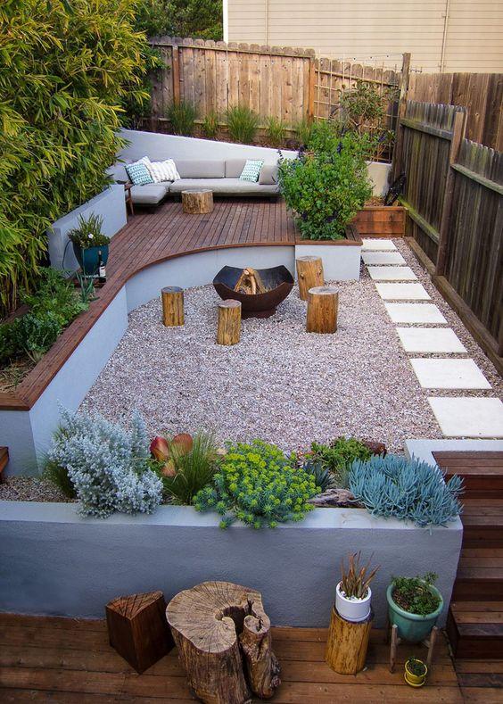 un patio ultramoderno con un ponte in legno con mobili, fioriere in cemento, ceppi d'albero e un pozzo del fuoco